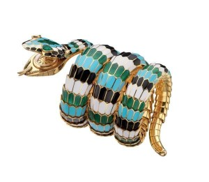 """Snake"" bracelet-watch in gold with polychrome enamel and emeralds, 1967. The flexible bracelet designed as a coiled snake, the scales decorated with white, black, green and turquoise enamel, the head with pear-shaped emerald eyes concealing a gold case, champagne coloured dial; applied gold baton-shaped indexes with black profiles, at 12 paired baton-shaped indexes; ""JAEGERLECOULTRE / BVLGARI / SWISS MADE"" logos printed in black; black sword-shaped hands; gold back-case with asymmetrical soleil finish secured by two screws; crown winder; hand-wound mechanical movement. Marks: on the reverse of the head: ""BVLGARI"" engraved; on the back-case: numbered ""1122607""."