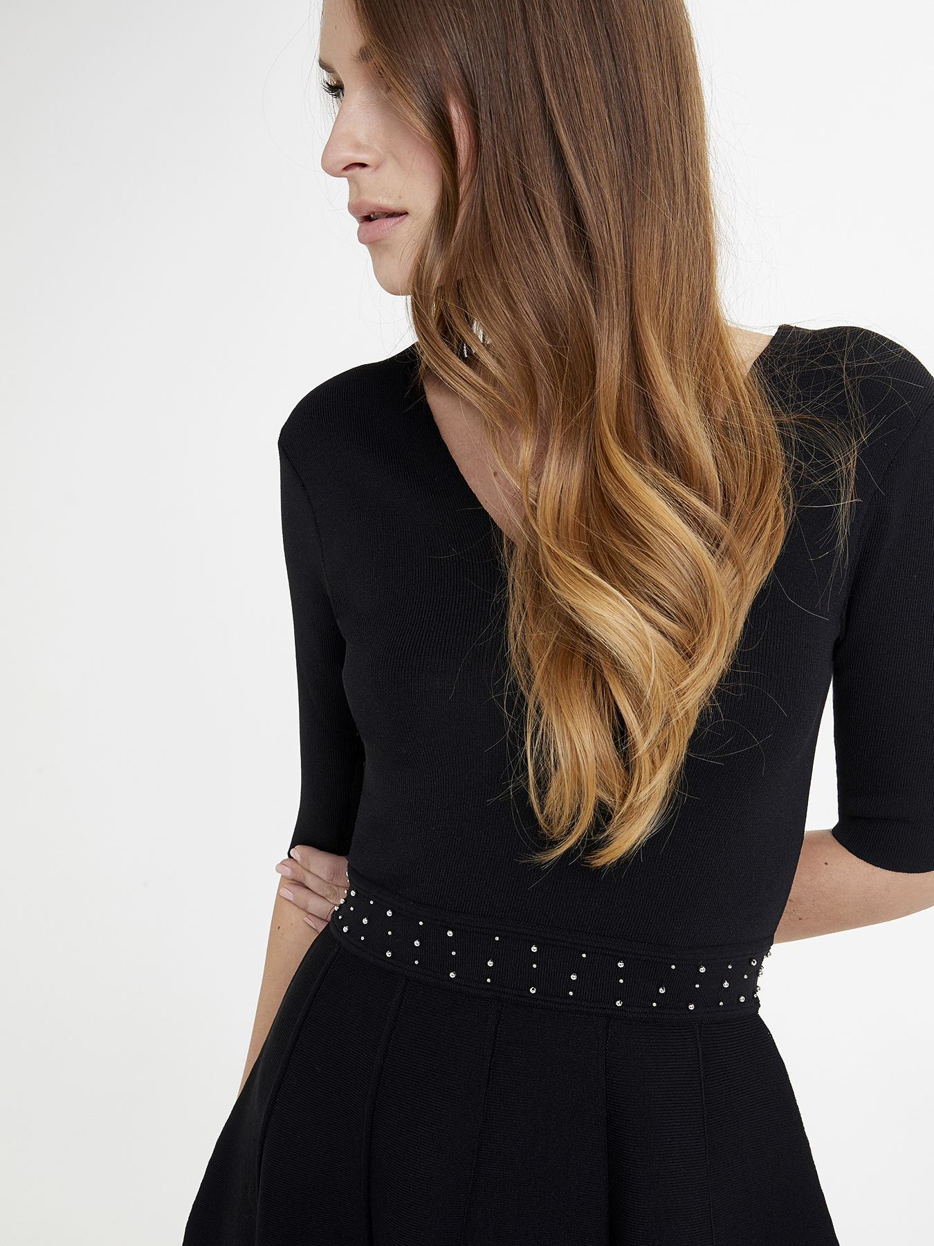Tricot-effect jersey dress with elbow sleeves and worked skirt; V-shaped neckline and flared line; waist with an embroidery of silver metallic pearls.